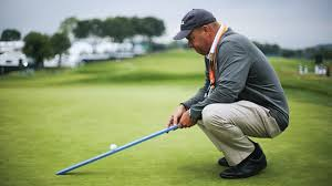 A greenkeeper measuring the green speed